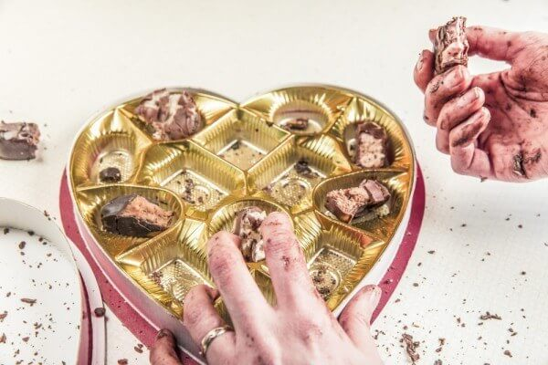 Half-eaten chocolates in heart-shaped box