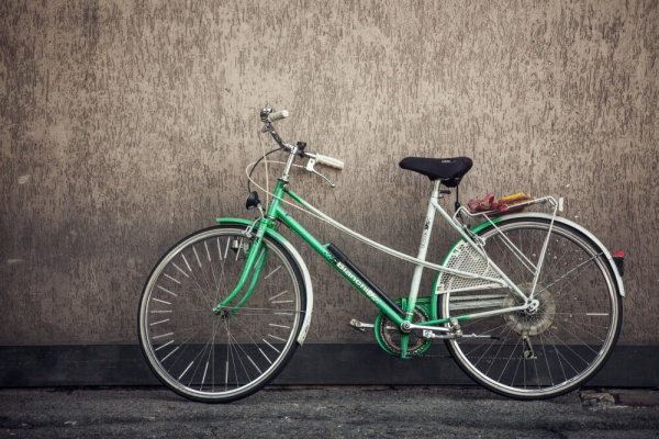 A green bike by a grey wall